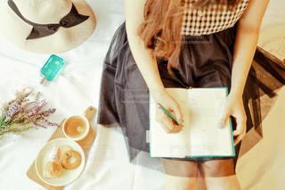 一杯のコーヒーをテーブルに座っている女性の写真・画像素材[2081035]