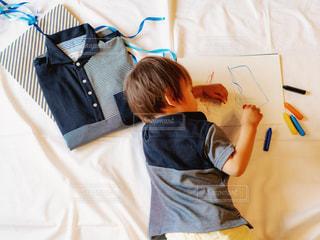 ベッドに横たわっている小さな男の子の写真・画像素材[2138799]