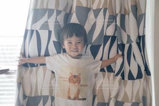 カーテンの前に立っている少年の写真・画像素材[2170841]