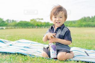 草の上に座っている小さな男の子の写真・画像素材[2214388]