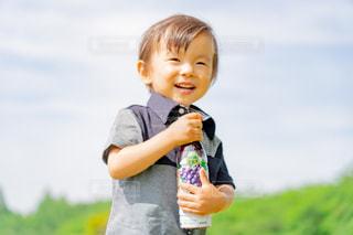 草の上に立っている小さな男の子の写真・画像素材[2214394]