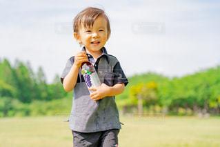 草の上に立っている小さな男の子の写真・画像素材[2218035]