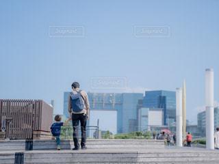 フェンスの隣に立っている人の写真・画像素材[2391757]