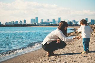 水域の近くの浜辺に立っている人の写真・画像素材[2391763]