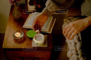 木製のテーブルの上でホットドッグを持っている人の写真・画像素材[2763621]