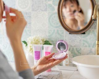 鏡の前のテーブルに座っている人の写真・画像素材[3018238]