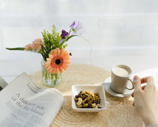 テーブルの上にコーヒーと花瓶を置いたの写真・画像素材[3026018]