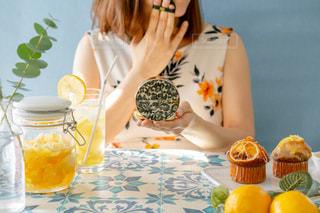 ケーキを持ってテーブルに座っている女性の写真・画像素材[3078998]
