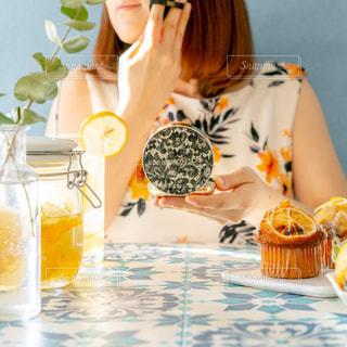 誕生日ケーキを持ってテーブルに座っている女性の写真・画像素材[3079002]