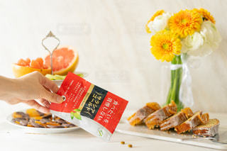 食べ物の皿と花瓶をテーブルの上に置くの写真・画像素材[3111009]