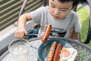 食べ物を食べている小さな男の子の写真・画像素材[3240080]