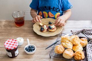 食べ物の皿を持ったテーブルに座っている人の写真・画像素材[3305180]