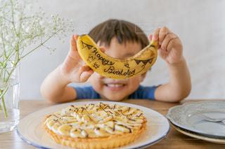 テーブルに座ってバナナを食べている小さな男の子の写真・画像素材[3331743]
