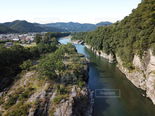 山の中腹に木と岩の多い川の写真・画像素材[768487]