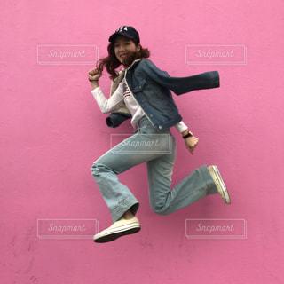 ピンクの壁の前でジャーンプ!の写真・画像素材[719715]