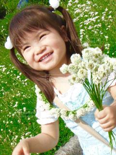 花を保持している小さな女の子の写真・画像素材[990135]