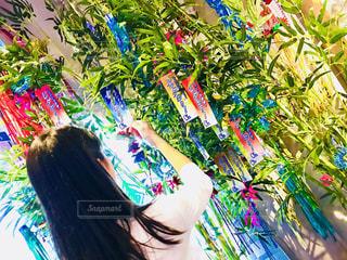 カラフルな花の前に立っている女性の写真・画像素材[1289137]