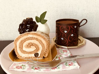 コーヒー カップの横にある皿の上のケーキの一部の写真・画像素材[1463660]