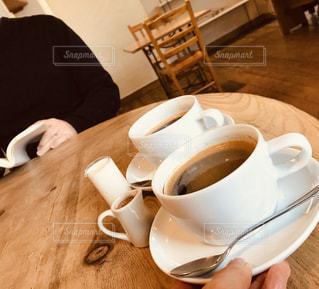 木製のテーブルの上に座っているコーヒーのカップの写真・画像素材[2901293]
