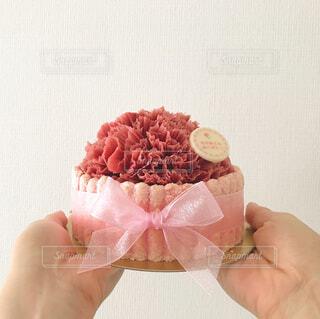 ピンクのケーキを持つ手の写真・画像素材[4402758]