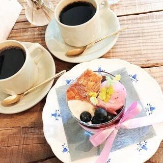 食べ物の皿と一杯のコーヒーをテーブルの上に置いての写真・画像素材[4958281]