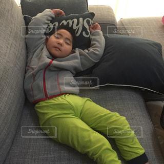 ソファーで横たわっている少年の写真・画像素材[990046]