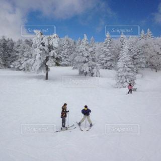 雪に覆われた斜面をスキーに乗っている人のグループ - No.931262