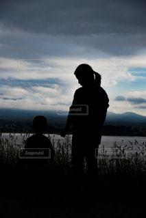 暗い曇り空に立っている人のグループ - No.731469