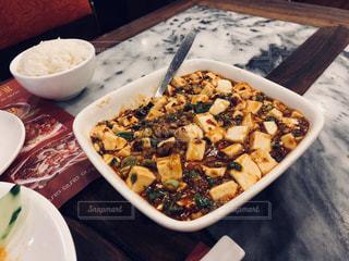 テーブルの上の皿の上に食べ物のボウルの写真・画像素材[889882]