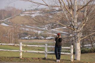 フェンスの横に立っている人の写真・画像素材[1279364]