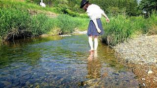 水の体の横に立っている人の写真・画像素材[1112975]