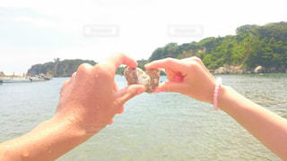 近くに水体でフリスビーを投げる人間のアップの写真・画像素材[1112992]