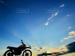 オートバイに乗りながら空を飛ぶ男の写真・画像素材[2422745]