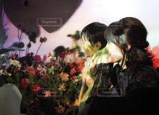 花の前に立っている女性の写真・画像素材[887633]