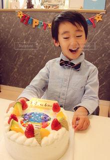 バースデー ケーキでテーブルに座っている人の写真・画像素材[1448336]