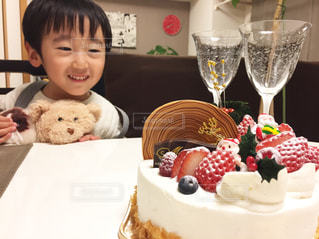 小さな男の子がケーキでテーブルに座っての写真・画像素材[1685842]