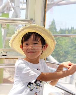 帽子をかぶって、カメラで微笑んでいる人の写真・画像素材[2104454]