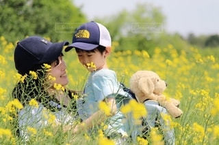 野原に黄色い花をつけた少年の写真・画像素材[2140707]
