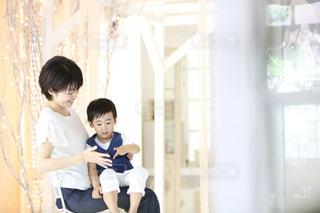 窓の隣に座っている若い男の子の写真・画像素材[2313709]