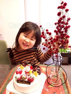 バースデー ケーキでテーブルに座っている女性の写真・画像素材[1695768]