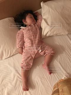 ベッドの上で横になっている少女の写真・画像素材[1230845]