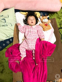 若い女の子がベッドで眠っています。の写真・画像素材[1230873]