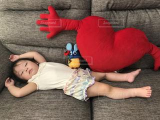 赤ちゃんのベッドの上に横になっているテディベアを保持 - No.1247815