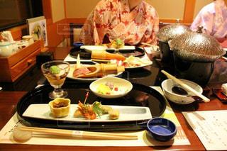 人の食べ物のプレートとのテーブルに座っての写真・画像素材[752460]