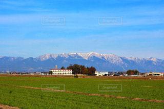 背景の山に大規模なグリーン フィールドの写真・画像素材[1393823]