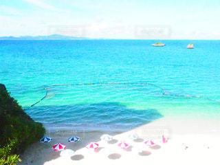 海の横にある砂浜のビーチの上に座っている青いフリスビー - No.923526