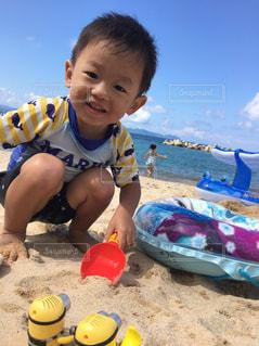 ビーチに座っている小さな男の子の写真・画像素材[705341]