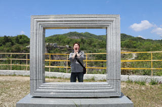フェンスの前に立っている男の写真・画像素材[816152]