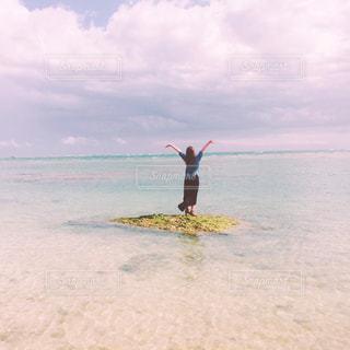 水の体の横に立っている人の写真・画像素材[1033400]