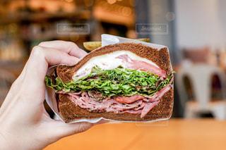 近くにサンドイッチを持っている人のの写真・画像素材[764235]